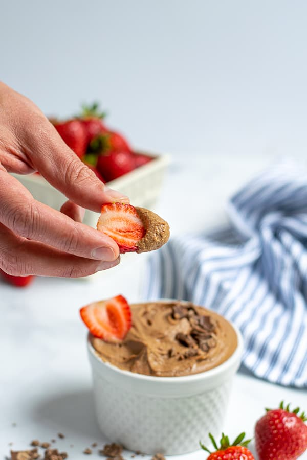 a hand holding a strawberry with a scoop of chocolate hummus on the end