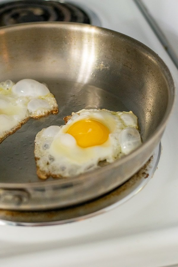 close up a an egg coking in a frying pan on a stove