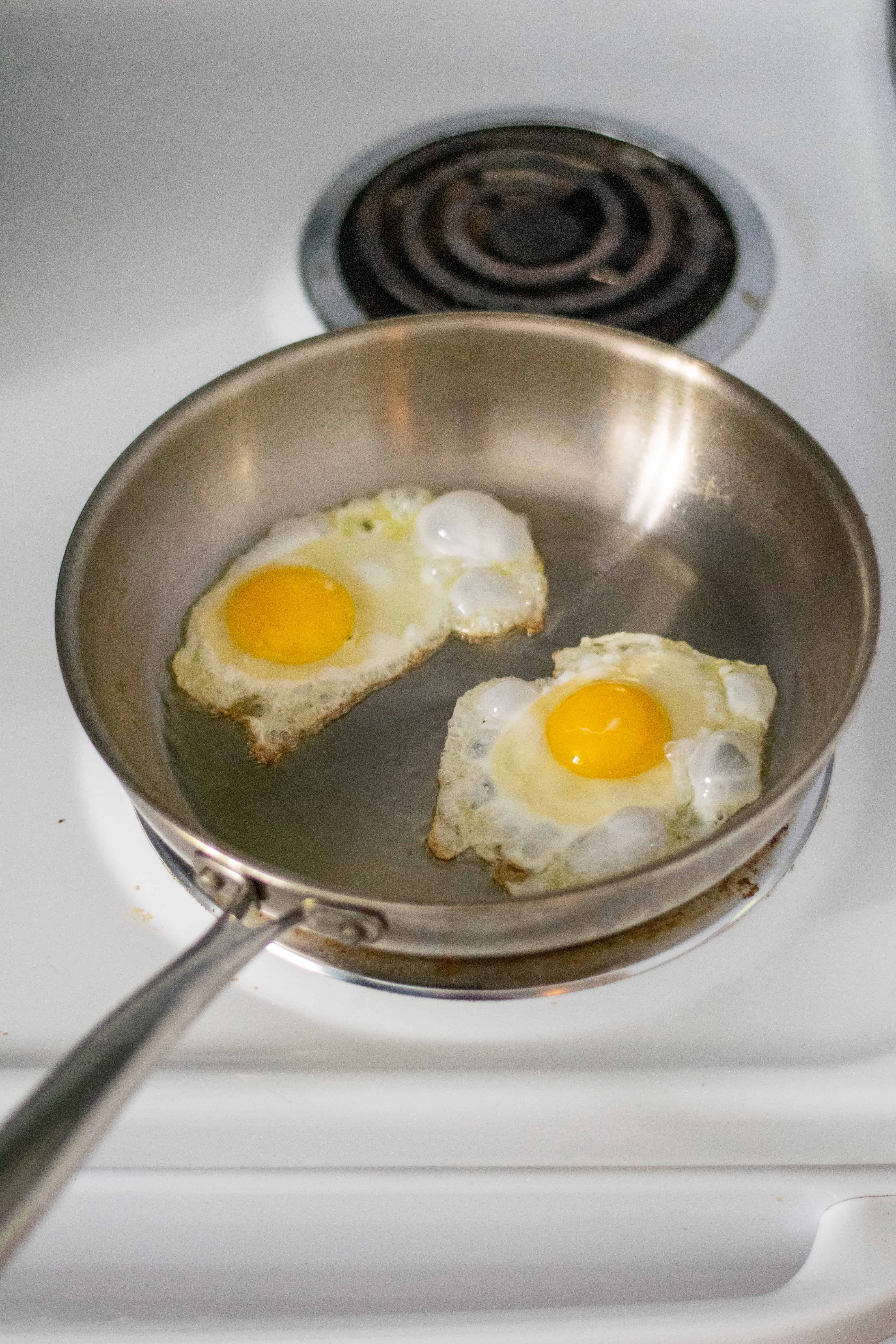 eggs in a frying pan on the stove top cooking