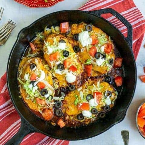 Taco Chicken Breasts in a cast iron skillet with lettuce, tomatoes, sour cream, and black olives
