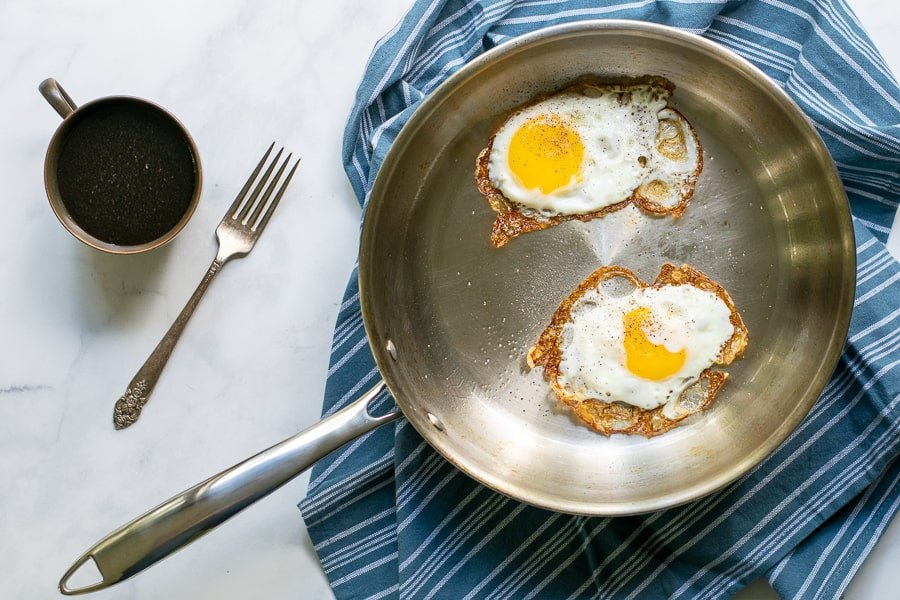 overhead photo of a stainless steel frying pan with two fried eggs in it