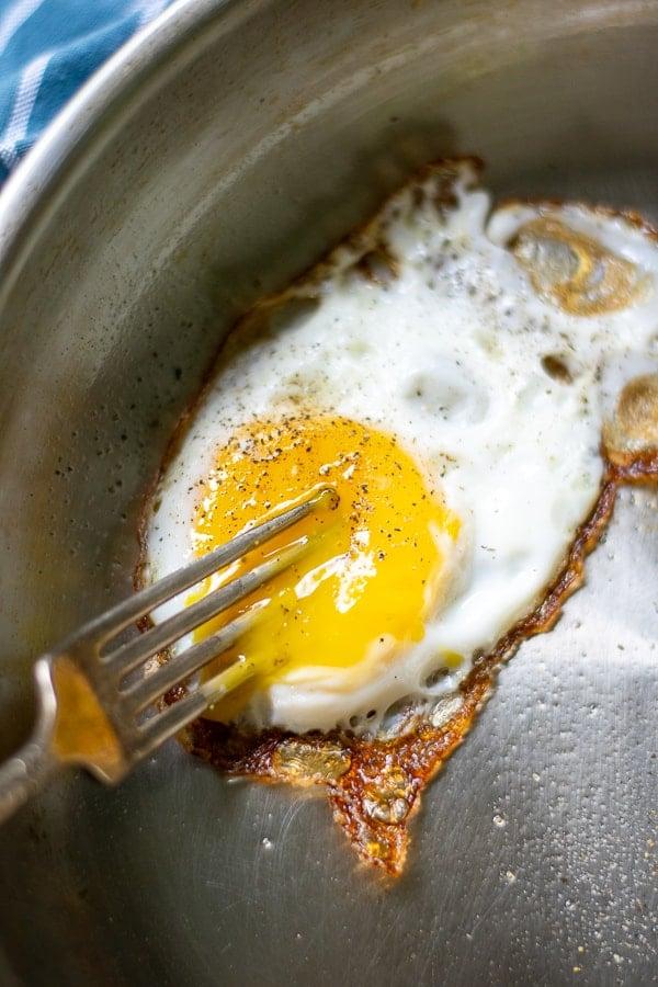 fork breaking a cooked egg yolk