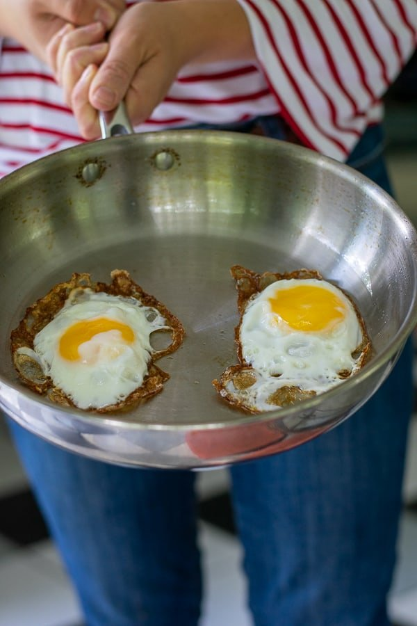 person holding a stainless steel frying pan with 2 fried eggs in it