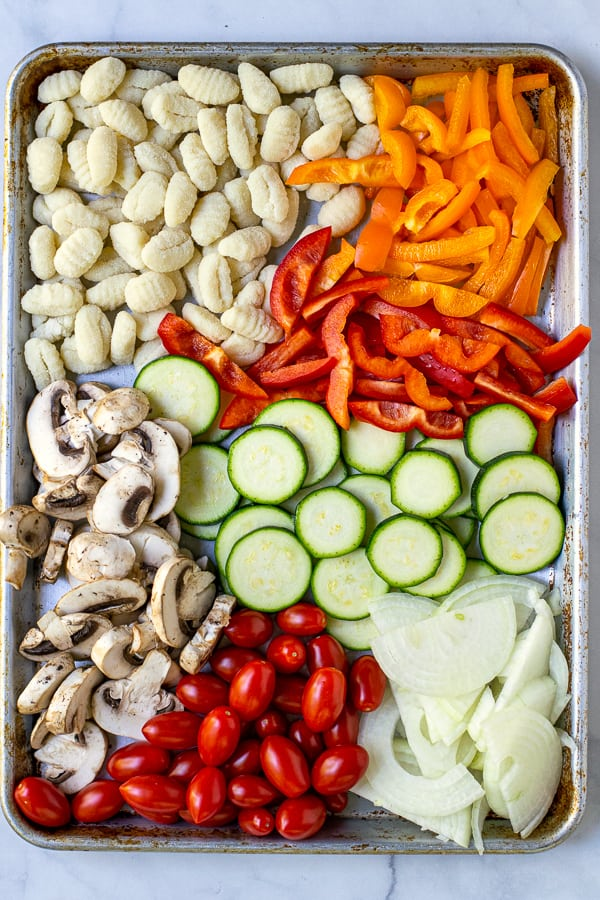prepped vegetables and gnocchi on a sheet pan before getting tossed