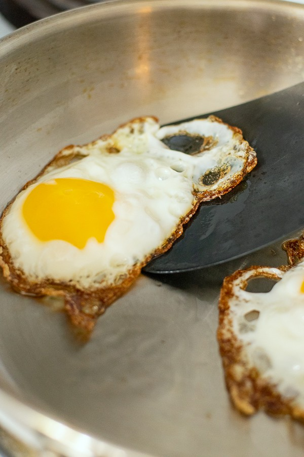 spatula under a fried egg in a frying pan