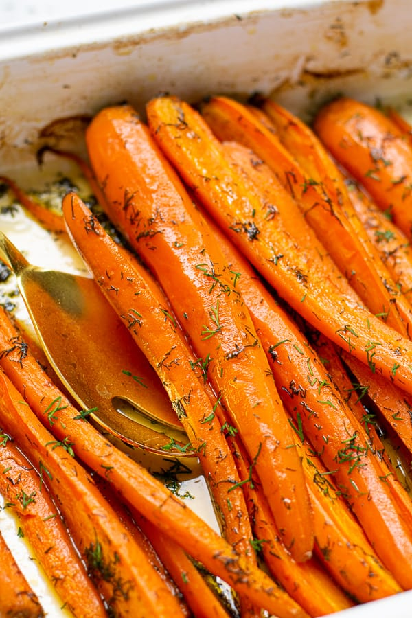 close up of roasted carrots with dill in a roasting pan