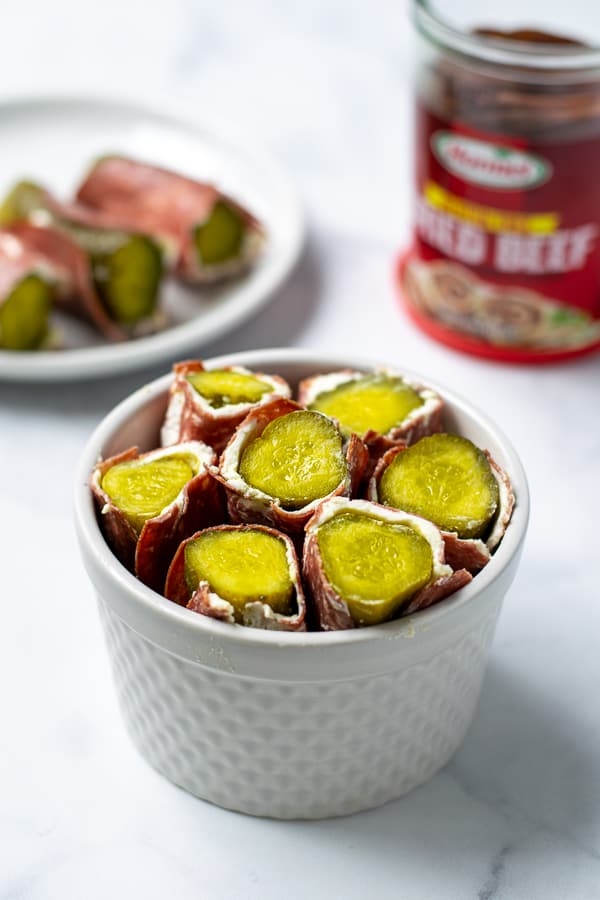 pickle roll ups with cream cheese and dried beef in a white bowl