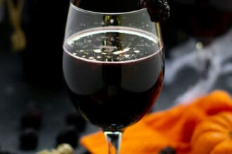 blackberry halloween sangria in a wine glass with fruit and pumpkins and skeletons on the table
