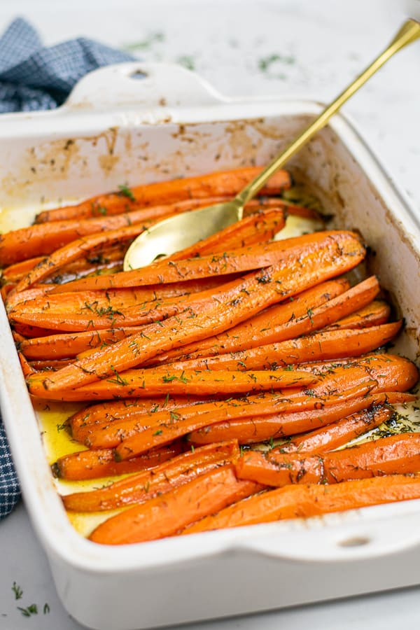 roasted carrots with dill and brown sugar in a white baking dish with a gold spoon