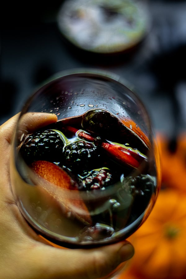 hand holding a glass full of fruits and black halloween sangria