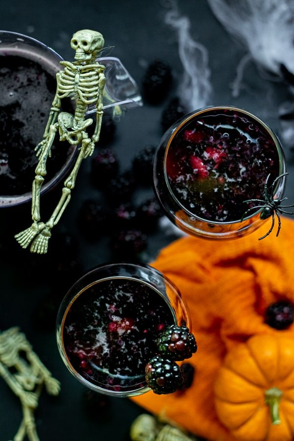 wine glasses full of black fruit and halloween sangria on a black table