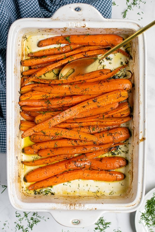 roasted carrots in a white baking dish sprinkled with fresh dill
