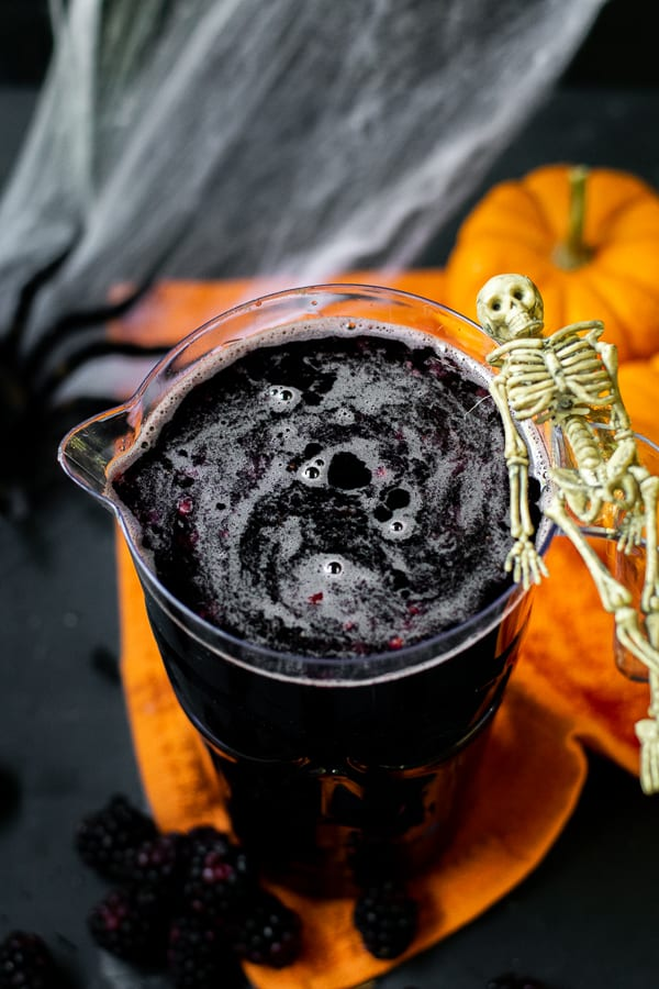 pitcher full of blackberry sangria with a skeleton hanging on the side