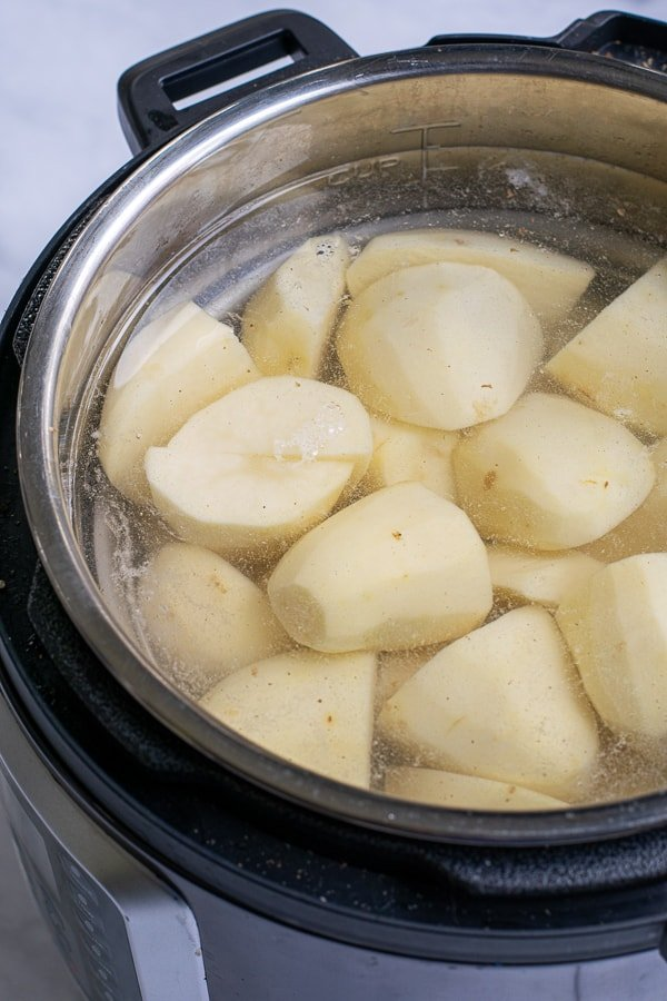 pressure cooker full of potatoes and water