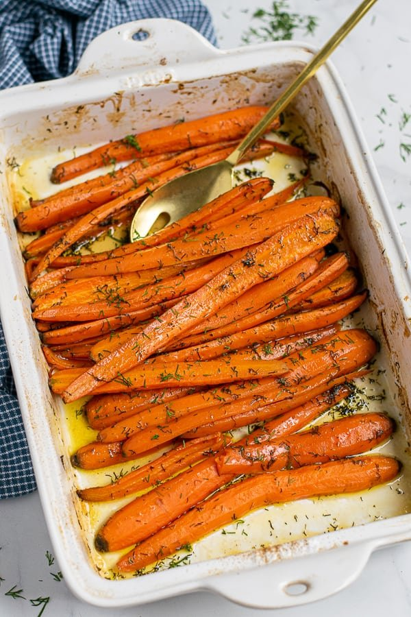 spoon in the white baking dish filled with roasted carrots