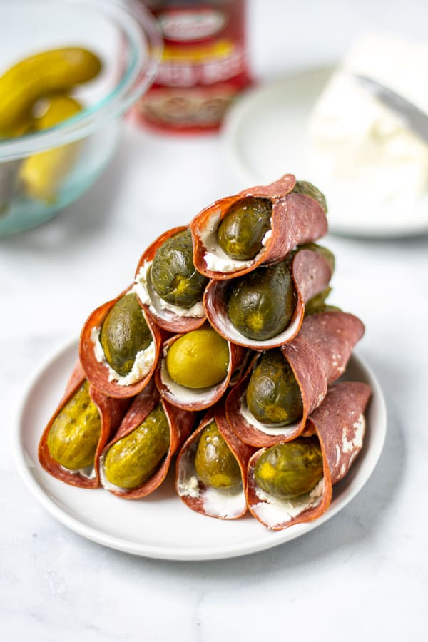 tall stack of dried beef pickle roll ups on a white plate