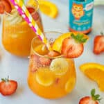 glass filled with fruit and orange juice with colorful straws
