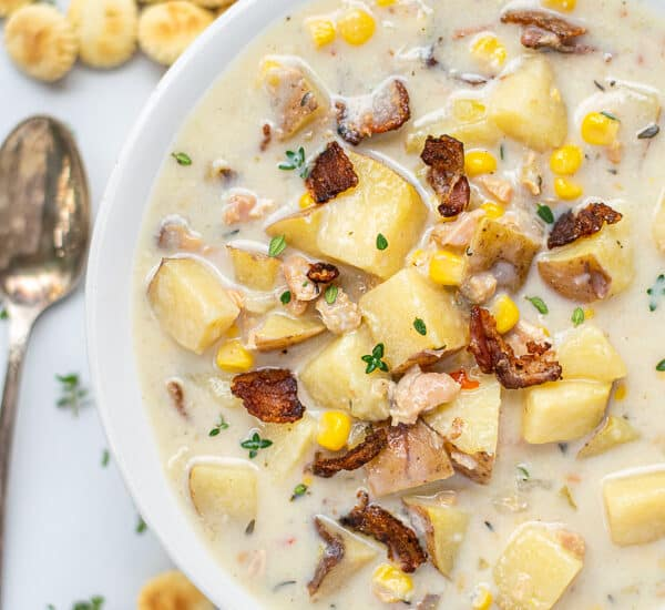 Healthy Clam Chowder in a white bowl with a spoon and oyster crackers