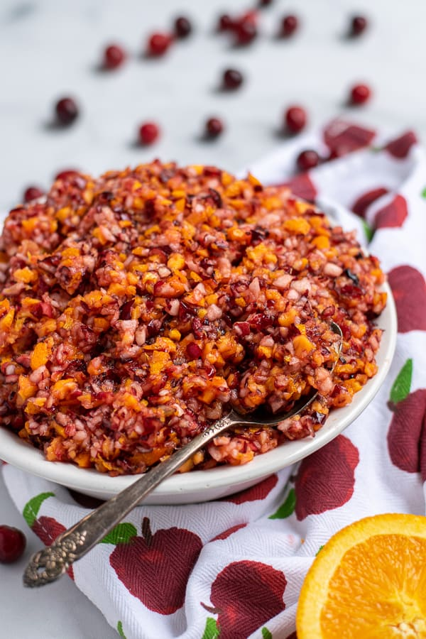 Cranberry Orange relish in a white bowl on a table with a spoon