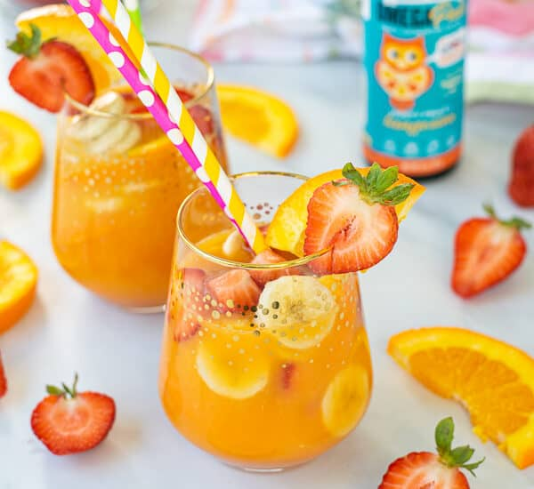 large glass of breakfast mocktail filled with fruits
