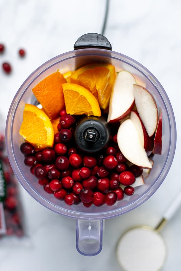 food processor with oranges, apples, and raw cranberries