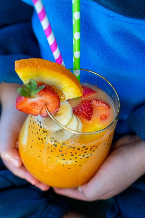 kids hands holding a glass of orange juice filled with colorful fruits