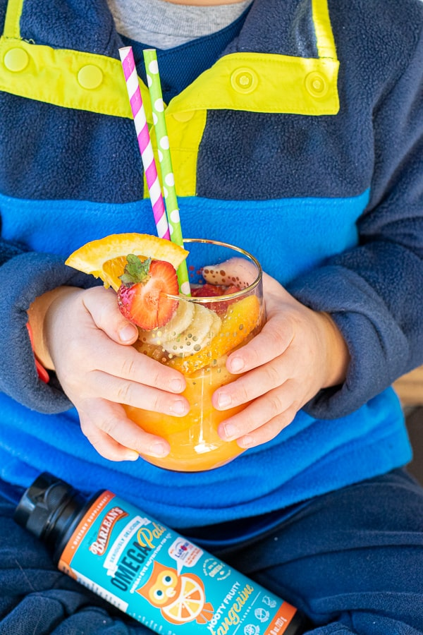 young kids holding an orange juice mocktail