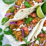 vegetarian red lentil tacos filled with garnishes are an easy weeknight meal