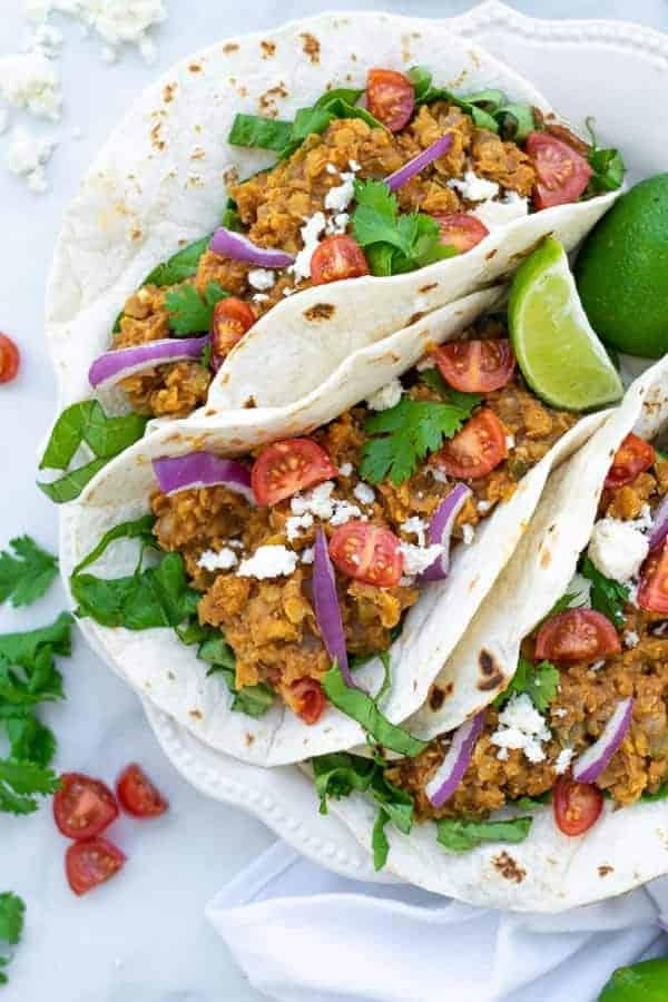 three red lentil tacos with vegetarian taco meat on a white plate with garnishes