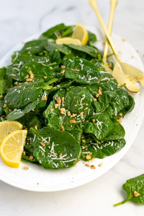a white platter full of simple spinach salad with cheese and walnuts
