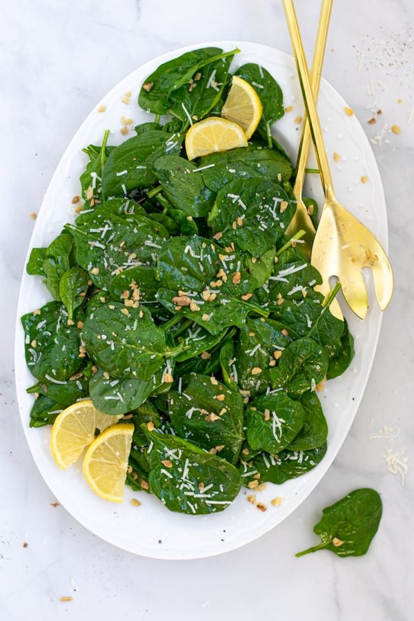 overhead view of a simple spinach salad on a white platter with gold serving utensils