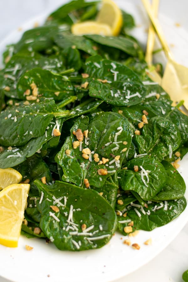 spinach salad on a white platter with lemon wedges, cheese, and nuts