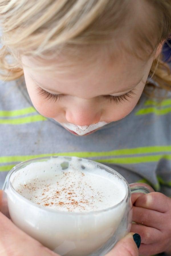 toddler going in for a sip of honey cinnamon milk steamer