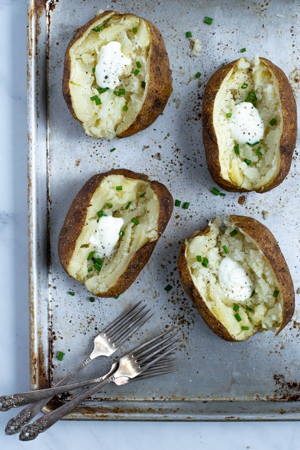 baked potatoes in a tray slices open with sour cream and chives