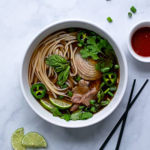 bowl of beef pho with bright green garnishes