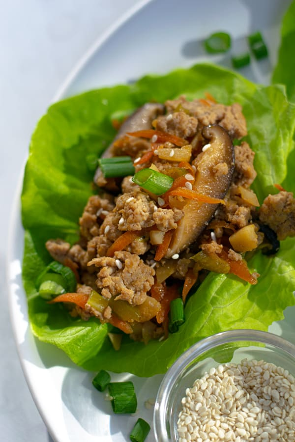 close up of the chicken filling on a lettuce wrap on a plate