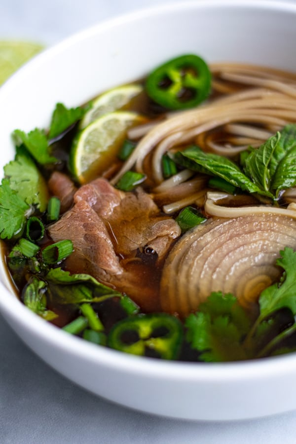 close up of steak, noodles, and garnishes in broth