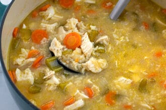 blue dutch oven filled with chicken and rice soup with a ladle full of soup