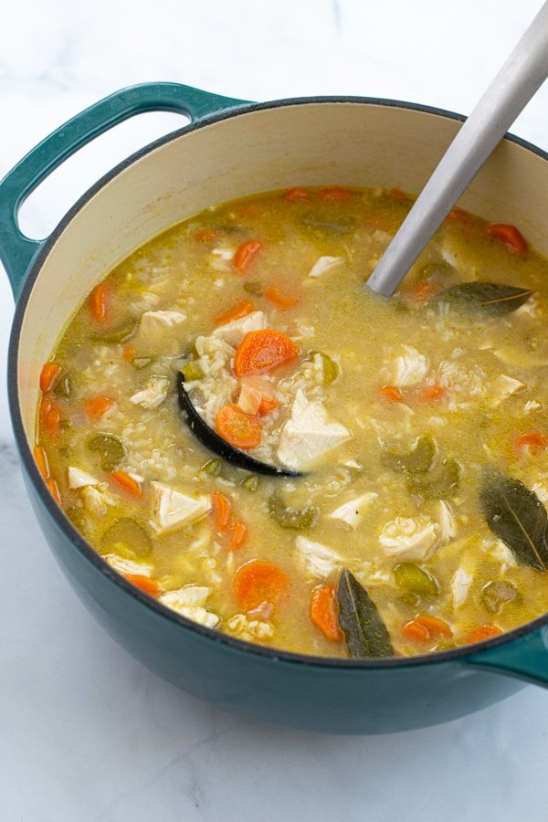 large blue dutch oven filled with freshly made chicken rice soup with a ladle