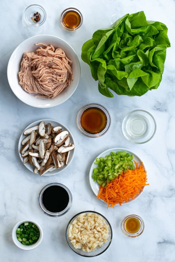 ingredients needed for asian chicken wraps including ground chicken, Bibb lettuce, and sauces
