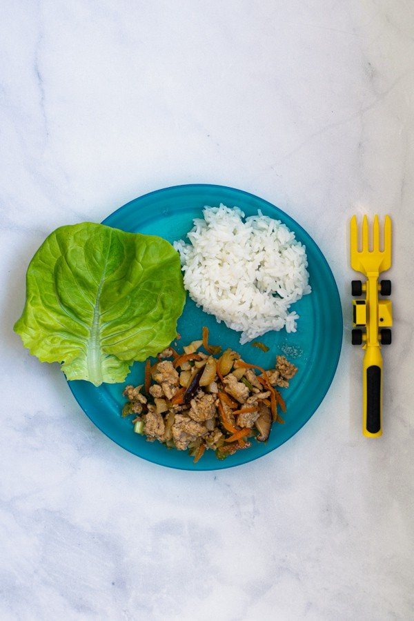 a blue kids plate with a construction truck fork with a kid size serving of asian chicken wraps