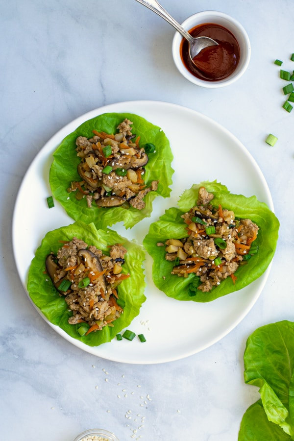plate with three ground chicken lettuce wraps with a bowl of sriracha