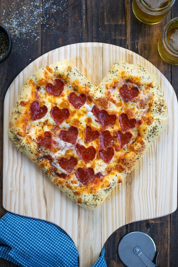 heart shaped pizza just pulled out of the oven on a pizza paddle with a pizza cutter and a couple of beers