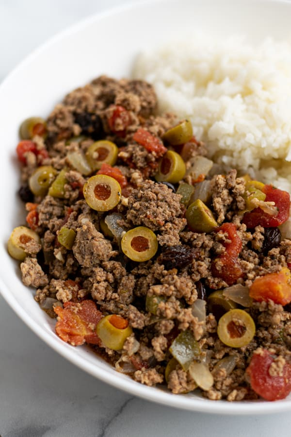 close up of cuban picadillo in a white bowl with rice