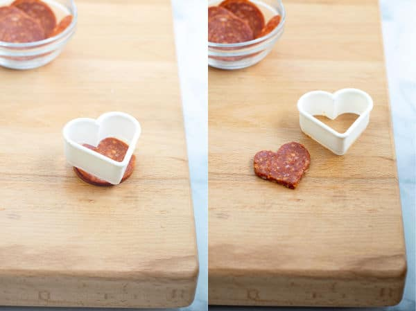 a small heart cookie cutter cutting pepperoni into a heart