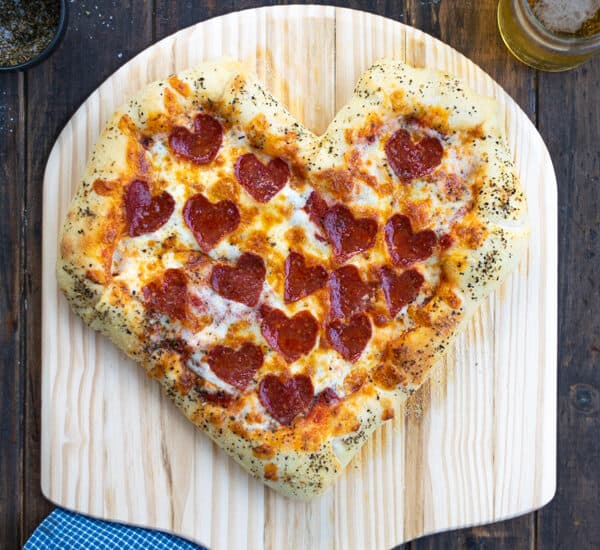 a freshly baked heart shaped pizza on a pizza paddle with heart shaped pepperoni