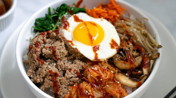 korean bibimbap bowl sitting on a table with chopsticks and kimchi
