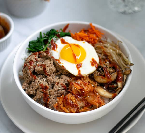 korean bibimbap bowl sitting on a table with chopsticks and kimchi