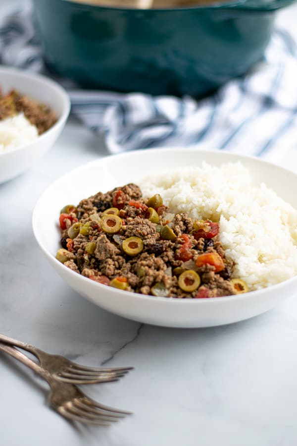 bowl of Cuban Picadillo with white rice on a table with forks