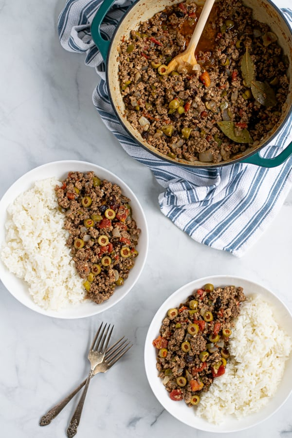 two bowls with rice and picadillo and a dutch oven filled with picadillo